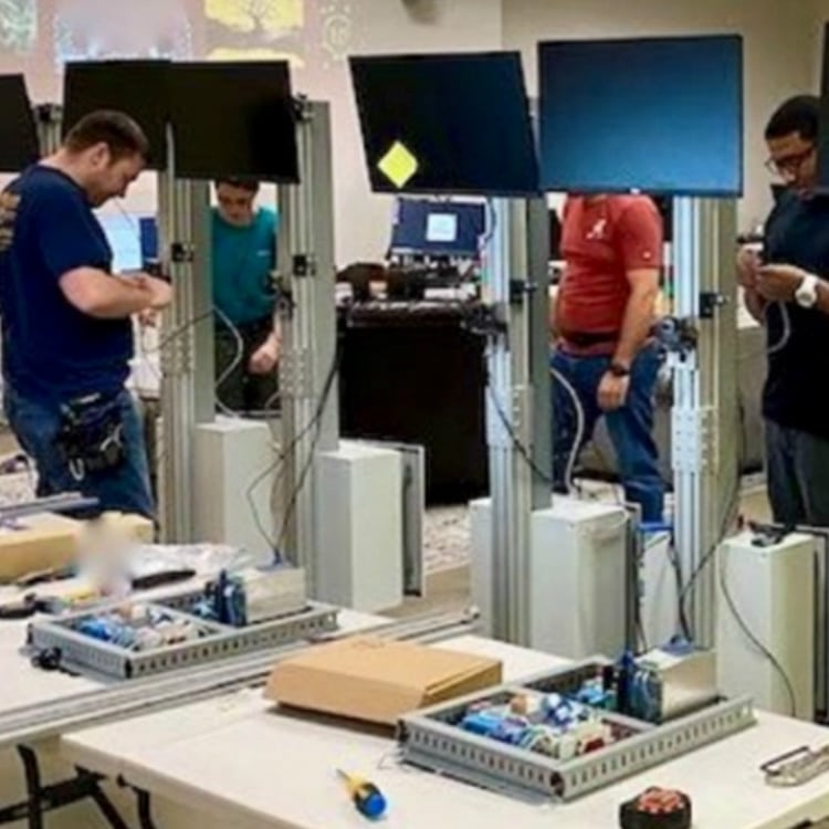 A Group Of People Standing Around A Computer
